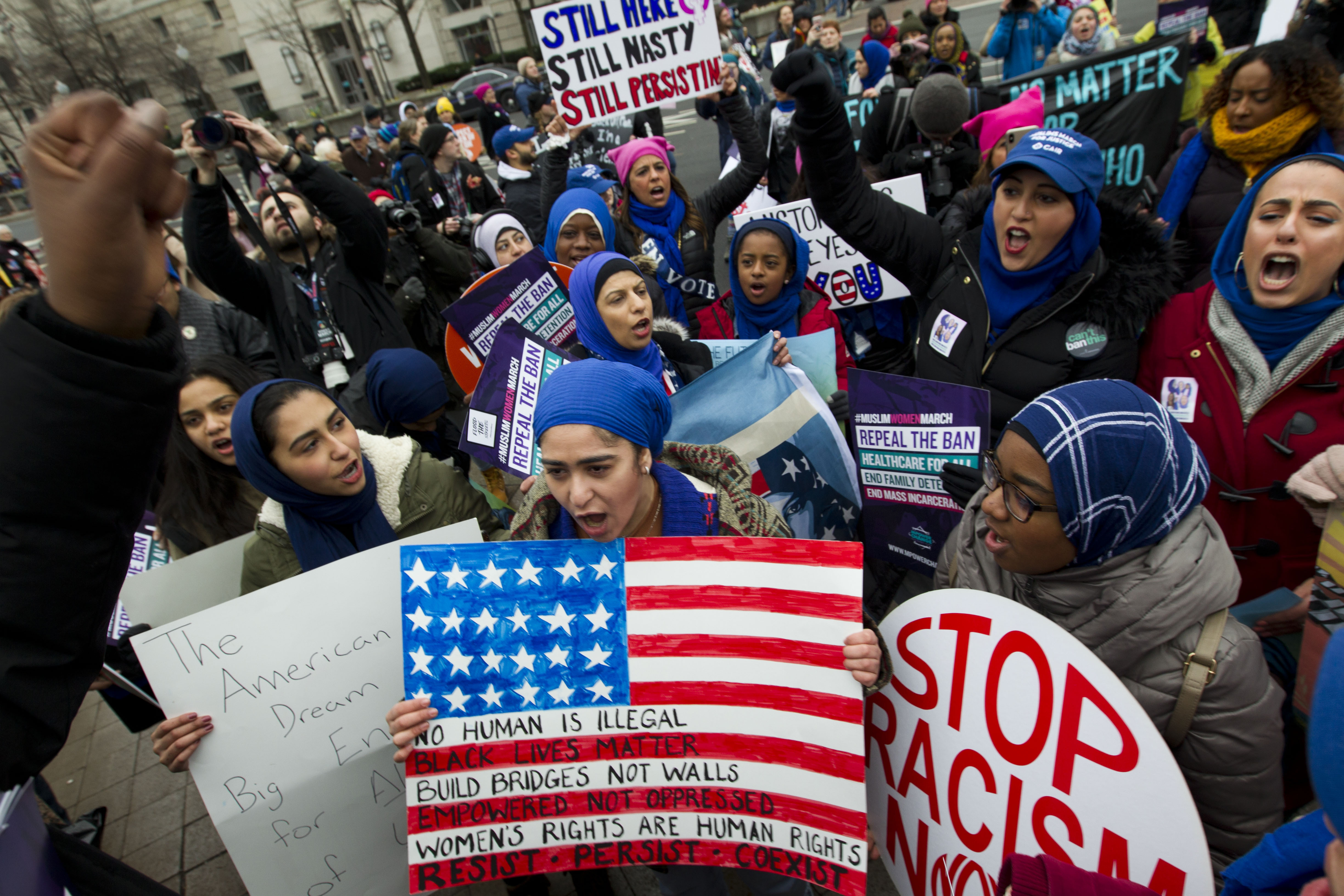 A group hold up signs at freedom plaza during the women's march in Washington on Saturday, Jan. 19, 2019. (AP Photo/Jose Luis Magana)