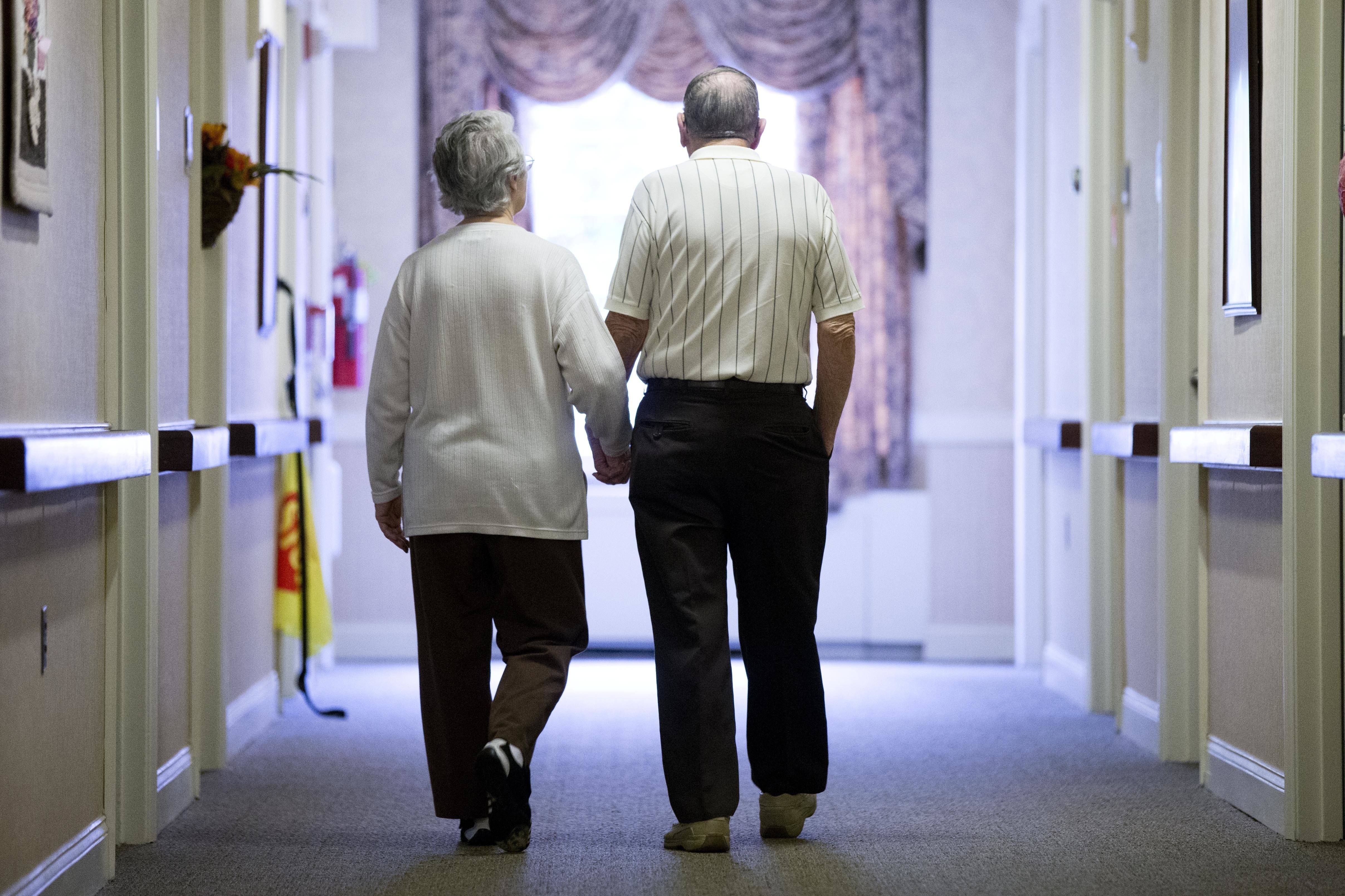 FILE - In this Nov. 6, 2015 file photo, an elderly couple walks down a hall of a nursing home in Easton, Pa. Research released on Tuesday, June 4, 2019 shows fatal falls have nearly tripled in older Americans in recent years, rising to more than 25,000 deaths yearly. (AP Photo/Matt Rourke, File)