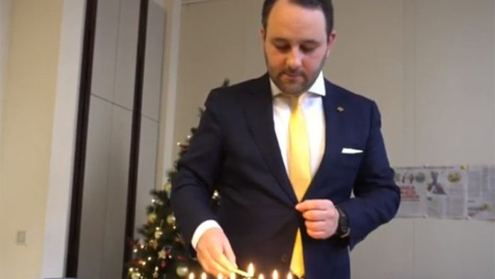 Michael Freilich lights Hanukkah candles in the Belgian Federal Parliament in Brussels, Belgium, Dec. 19, 2019. (Michael Freilich)