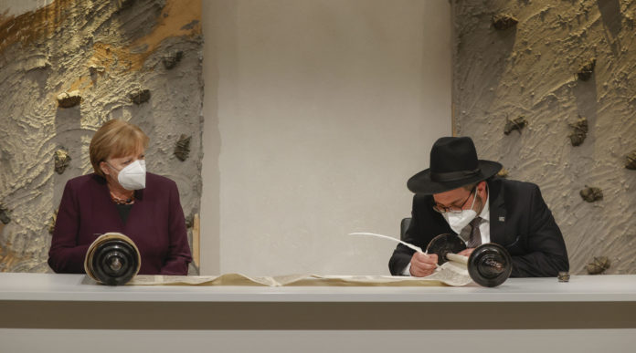 German Chancellor Angela Merkel watches Rabbi Shaul Nekrich complete the historic Sulzbach Torah Scroll in Berlin, Jan. 27, 2021. (Odd Andersen/Pool/Getty Images)