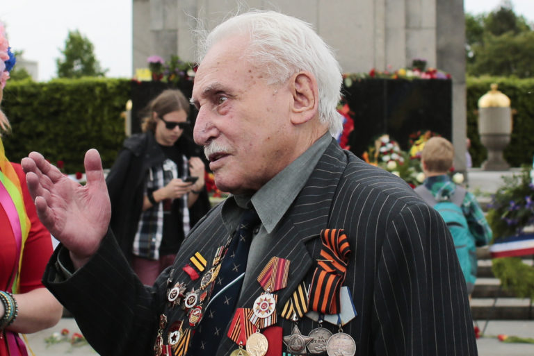 FILE - In this Friday, May 8, 2015 file photo, Soviet war veteran David Dushman, 92, center, speaks to people holding Ukrainian flags as he attends a wreath laying ceremony at the Russian War Memorial in the Tiergarten district of Berlin, Germany. Dushman, the last surviving Allied soldier involved in the liberation of Auschwitz, has died. The Jewish Community of Munich and Upper Bavaria said Sunday, June 6, 2021 that Dushman had died a day earlier in a Munich hospital at the age of 98. As young Red Army soldier, Dushman flattened the forbidding fence around the notorious Nazi death camp with his tank on Jan. 27, 1945. (AP Photo/Markus Schreiber, File)