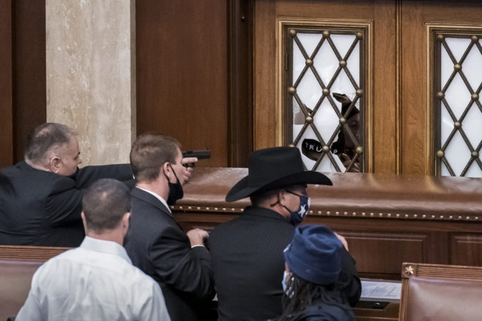 FILE - In this Jan. 6, 2021, file photo security agents and lawmakers barricade the door to the House chamber as a violent mob loyal to then President Donald Trump breach the Capitol in Washington and disrupt the Electoral College process. A New York mother and son have been charged with theft in aiding the disappearance of House Speaker Nancy Pelosi's laptop during the Jan. 6 insurrection after the FBI initially raided a home 4,500 miles away in Alaska, looking for the computer. According to court documents, the FBI on Friday, Oct. 1 arrested Maryann Mooney-Rondon, and her son, Rafael Rondon, of Watertown, N.Y. Both also face other charges related to the riot at the Capitol. (AP Photo/J. Scott Applewhite, File)